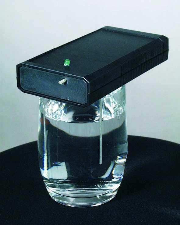 Ein Generator zur Herstellung von kolloidalem Silber liegt auf einem Wasserglas